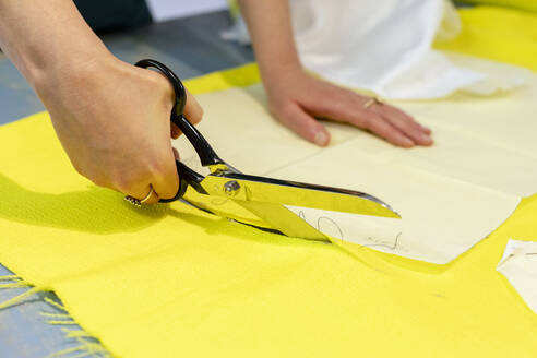 Hands of fashion entrepreneur cutting fabric at design studio - EIF00093