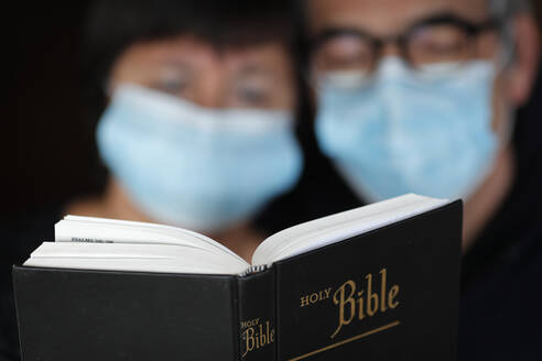 Man and woman reading the bible with a disposable mask to avoid contagious coronavirus (COVID-19), France, Europe - RHPLF15392