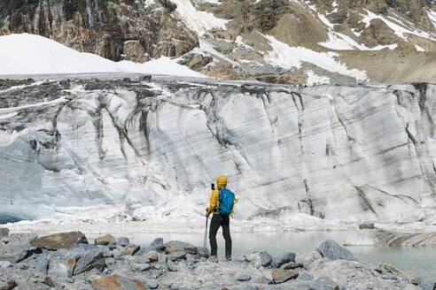 Man hiking while looking at melting glacier - MCVF00504