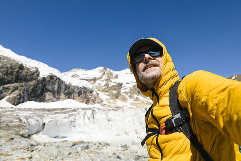 Smiling mature man standing against snowcapped mountain - MCVF00510