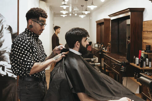 Trendy barber fixing cape on male client at salon - XLGF00381