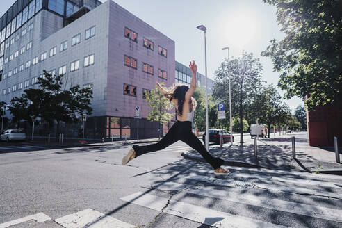 Excited young woman jumping on city street during sunny day - MEUF01303