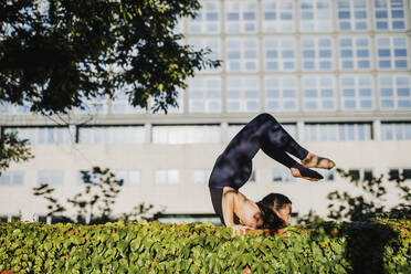 Young woman performing yoga on grass in city park during sunny day - MEUF01321