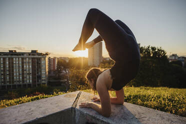 Flexible young woman performing yoga on retaining wall in city during sunset - MEUF01330