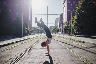 Young woman performing handstand on tramway in city during sunny day - MEUF01333