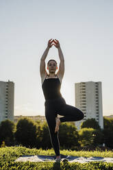 Young woman practicing yoga in tree pose at city park against clear sky - MEUF01342
