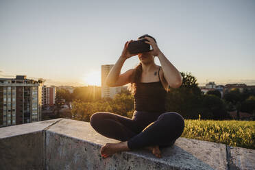 Sporty woman using VR glasses while sitting on retaining wall in city during sunset - MEUF01348
