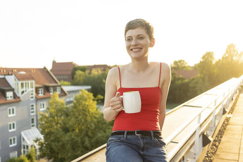 Smiling woman with short hair holding tea mug while sitting on railing in balcony at sunset - TAMF02527