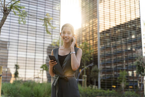 Smiling businesswoman holding smart phone while standing against modern buildings in city - AFVF06730