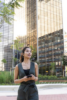 Businesswoman holding smart phone contemplating while standing against modern buildings in city - AFVF06733