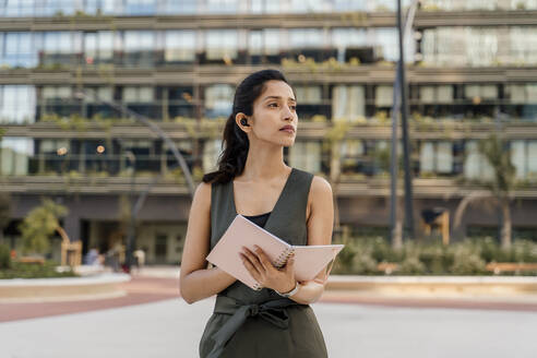 Thoughtful businesswoman holding note pad looking away while standing in city - AFVF06739
