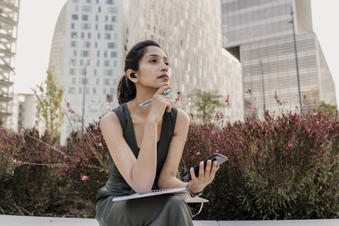 Thoughtful female professional with smart phone and note pad sitting by plants - AFVF06748