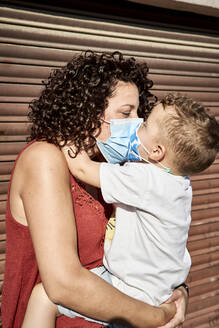 Mother carrying son with masks kissing him while standing against closed shutter - VEGF02509