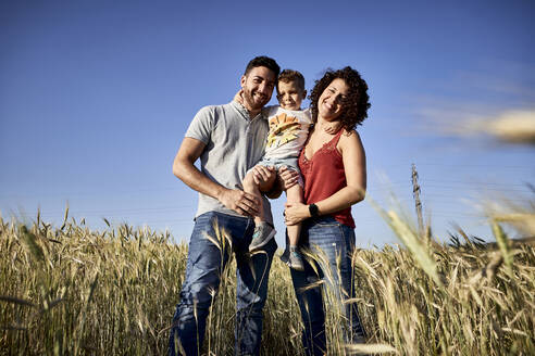 Smiling parents carrying son while standing amidst crops against clear blue sky - VEGF02527