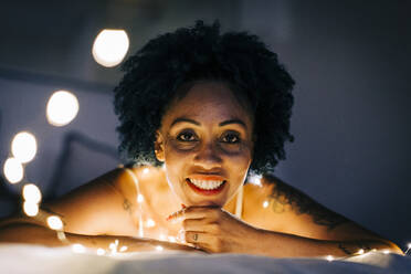 Close-up of smiling woman with illuminated string lights relaxing on bed at home - DCRF00396