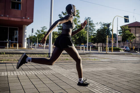 Female athlete listening music through headphones while running on street in city - MEUF01397