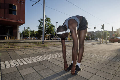 Female athlete listening music while exercising on road against clear sky in city - MEUF01409