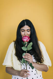 Young woman in front of yellow wall smelling rose - DCRF00416