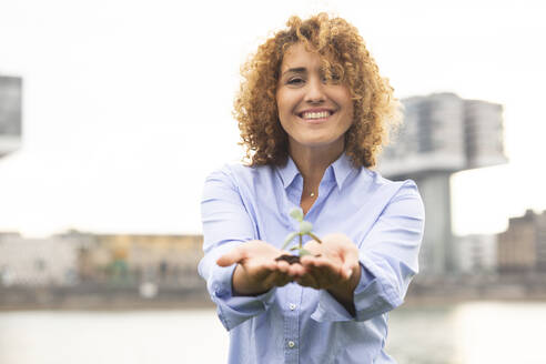 Smiling businesswoman with curly hair holding sapling while standing against sky in city - MJFKF00500