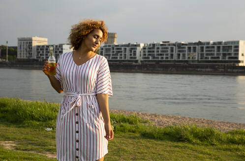 Mid adult woman holding beer bottle standing on grassy land against river in city at sunset - MJFKF00518