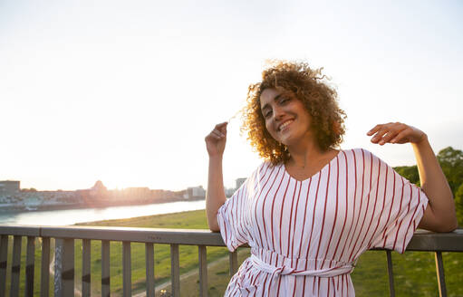 Smiling mid adult woman with curly hair leaning on railing against sky at sunset - MJFKF00527