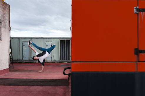 Man breakdancing on abandoned building terrace against sky - JMPF00193