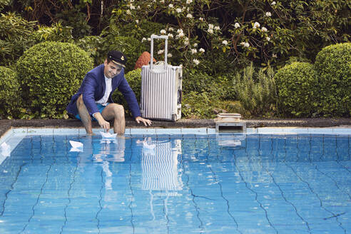 Man floating paper boats on swimming pool while sitting with suitcase against plants in yard - UKOF00005