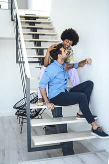 Affectionate multi-ethnic couple sitting on floating stairs in modern penthouse - EHF00573