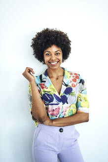 Happy mid adult woman with afro hairstyle standing against white background - EHF00576