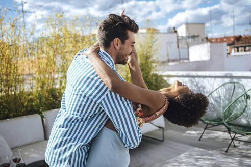 Cheerful multi-ethnic couple dancing on penthouse patio during sunny day - EHF00615