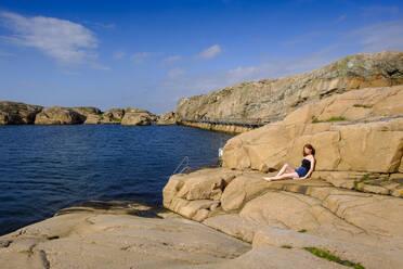 Frau sitzt auf Steinen und genießt die Sonne, am Vallevik Badplats, Badeplatz, Schärenlandschaft, Felsenküste, Schärenküste, Smögen, Schären, Provinz Bohuslän, Provinz Västra Götalands län, Südschweden, Schweden, - LBF03163