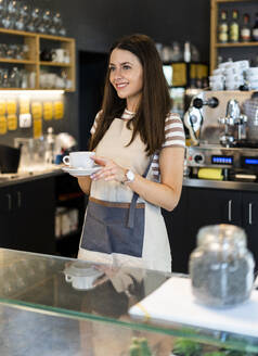 Happy female owner holding coffee cup and saucer while standing at counter in cafe - GIOF08553