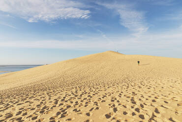Mid distance view of man walking on sand dune against sky, Dune of Pilat, Nouvelle-Aquitaine, France - GWF06633