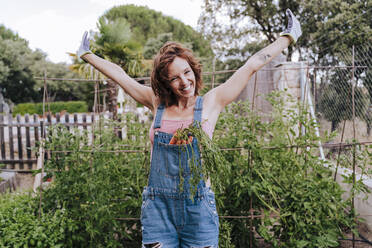 Cheerful woman with arms raised standing against plants in vegetable garden - EBBF00426