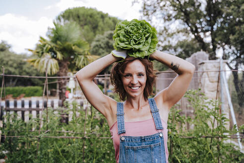 Smiling woman holding lettuce on head while standing in vegetable garden - EBBF00429