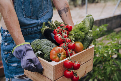 Close-up of woman holding wooden crate with various vegetables while standing in community garden - EBBF00435