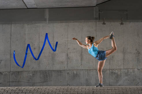Young woman spinning ribbon standing on one leg against concrete wall under bridge - STSF02566