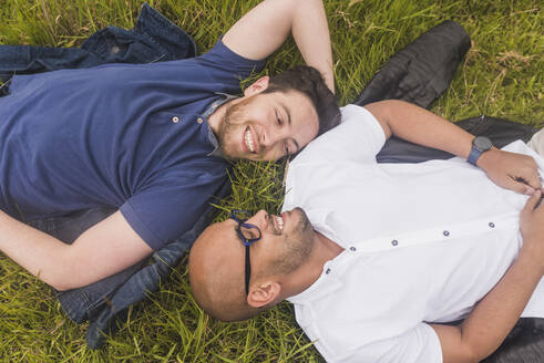 Smiling gay couple looking at each other while lying on grassy land in park - DSIF00026