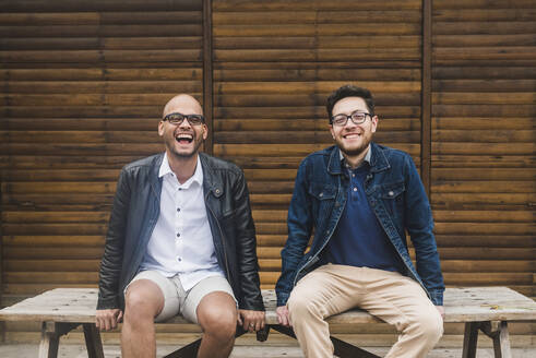 Cheerful gay couple sitting on table against wooden wall - DSIF00032