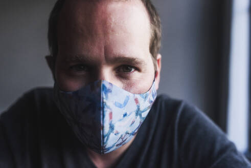Close-up of mid adult man wearing mask against wall at home - DSIF00035