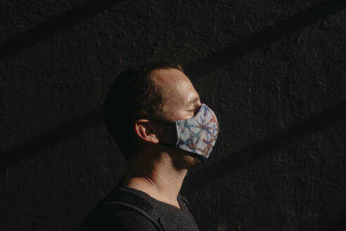 Close-up of mid adult man with eyes closed wearing mask against wall - DSIF00038