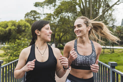 Smiling female friends jogging in park - DSIF00042