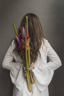 Woman with brown hair holding bouquet behind back by wall - DSIF00047