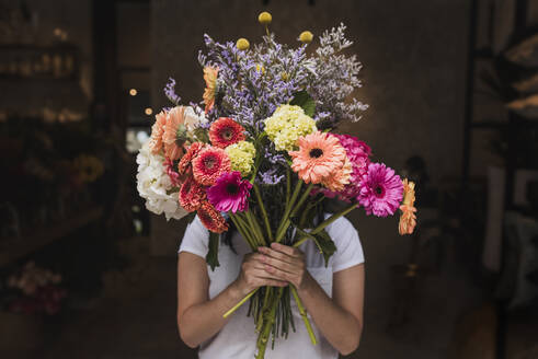 Female florist holding colorful flowers while standing in shop - DSIF00053