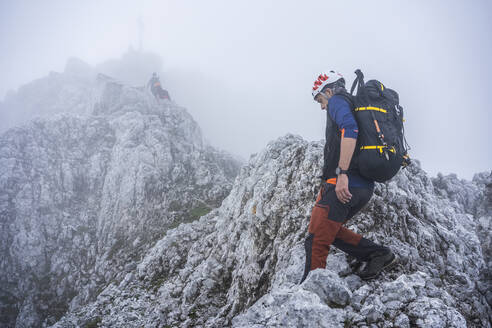 Mature males hiking on rocky mountains against sky during foggy weather, Bergamasque Alps, Italy - MCVF00540
