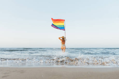 Mature woman on the beach with gay pride flag, rear view - CJMF00306
