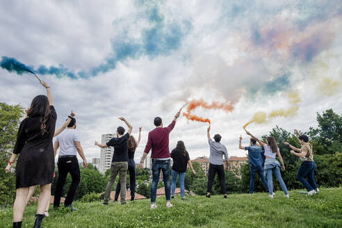 Carefree friends playing with smoke bombs against cloudy sky in park - MEUF01536
