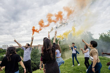Carefree friends playing with smoke bombs in park during weekend - MEUF01539