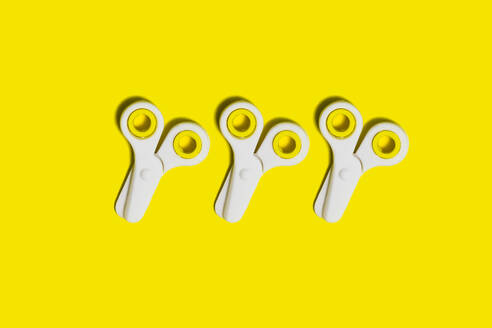 Studio shot of three pairs of school scissors against yellow background - XLGF00386