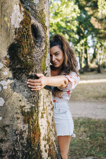 Smiling young woman holding tree trunk while standing in park - DCRF00477